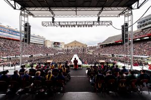Pictured from the back of the stage, Chancellor Rebecca Blank addresses graduates and their families during UW-Madison's spring commencement ceremony at Camp Randall Stadium at the University of Wisconsin-Madison on May 14, 2016. The outdoor graduation was attended by approximately 5,600 bachelor's and master's degree candidates and their guests. (Photo by Jeff Miller/UW-Madison)