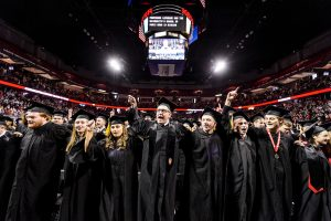 """Graduates link arms to sing """"Varsity"""" at the end of UW-Madison's winter commencement ceremony at the Kohl Center at the University of Wisconsin-Madison on Dec. 18, 2016. The indoor graduation was attended by approximately 1,000 bachelor's and master's degree candidates, plus their guests. (Photo by Jeff Miller/UW-Madison)"""