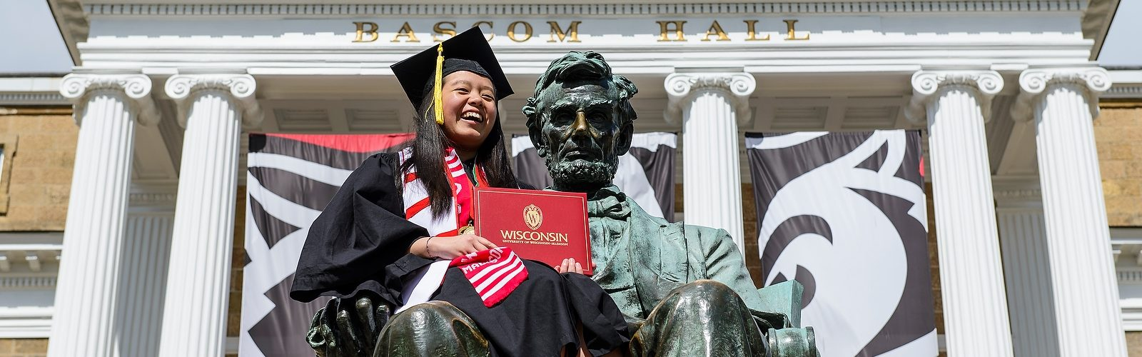 Soon-to-be-graduate Yer Thor is pictured on the Abraham Lincoln statue in front of Bascom Hall before the start of UW-Madison's spring commencement ceremony at Camp Randall Stadium at the University of Wisconsin-Madison on May 14, 2016. The outdoor graduation is expected to be attended by approximately 5,600 bachelor's and master's degree candidates and their guests. (Photo by Bryce Richter / UW-Madison)