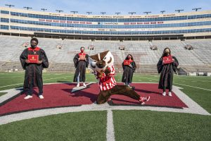 Senior Class officers pose with bucky at Camp Randall Stadium