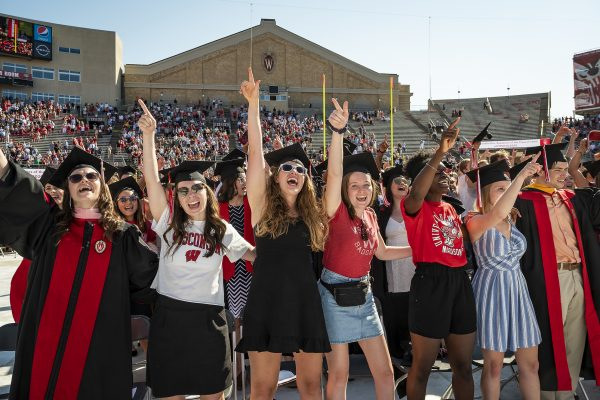 Class of 2020 graduates wearing mortar boards and casual attire, celebrate on the Camp Randall field.